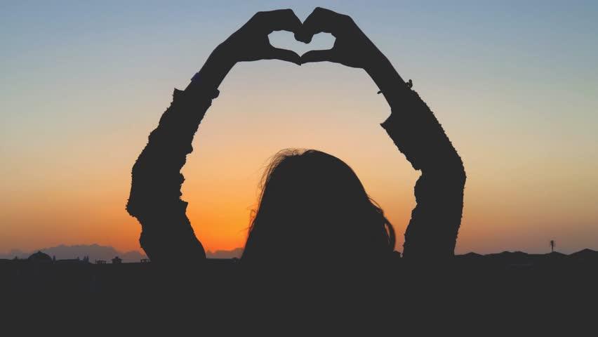 Girl holding heart shape in the sunset / sunrise time.