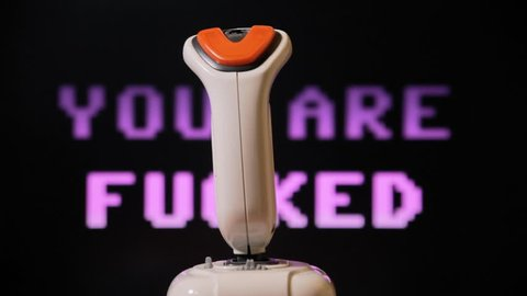 Playing with a retro vintage joystick (input device for computer games), 8-bit messages appearing on screen: Game Over, You Are Fucked.