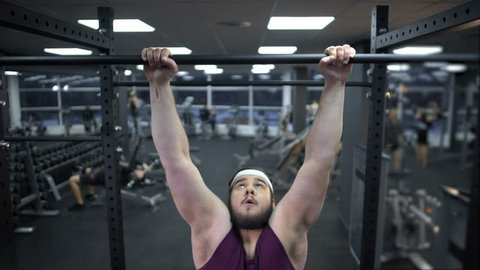 Chubby man pulling up on bar, desire to lose weight and be strong, motivation