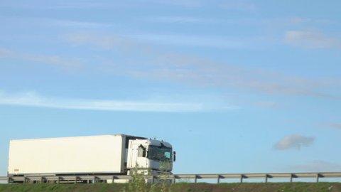 Cargo truck travel on inter city highways. International cargo transportation. Truck car drives through the bridge.