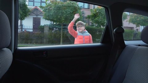 Elementary-school student goes to school. The boy out of the car and waving to his parents