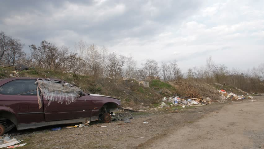Panoramic view of illegal garbage dump with old abandoned rusted cars in city. Trash and construction waste polluting city area. Environmental problems and pollution concept.