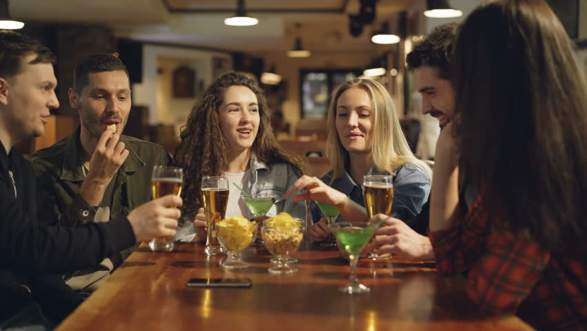 Cheerful young people are eating, drinking, chatting and laughing at table in modern cafe. Mates are wearing casual clothes. Snacks and glasses in foreground. | Shutterstock HD Video #1010554454