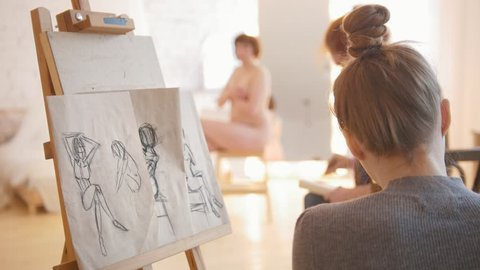 Two female artists sketching nude model in bright drawing class