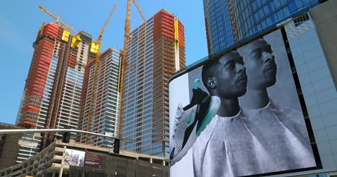 LOS ANGELES, CALIFORNIA, USA - APRIL 22, 2018: New construction development with cranes near electronic digital billboards in Los Angeles Downtown, California, USA, 4K