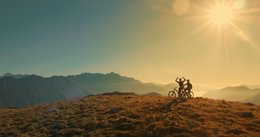 Aerial tracking wide shot of friends mountain biking in the sunset light with amazing peaks in background. | Shutterstock HD Video #1010578184