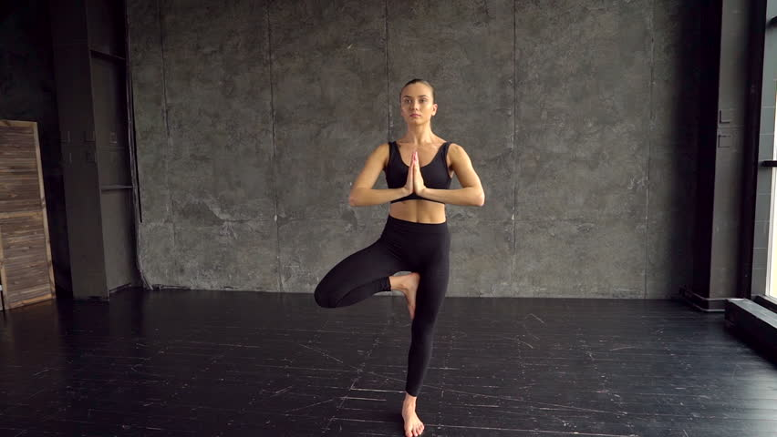 Peaceful girl with toned body performs the asanas. A lot of light in the room. Enlightenment. Meditation. Spiritual practice. The spiritual mentor. Tree pose. Try to keep balance. Young slim sporty #1010581214