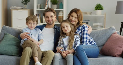 Good looking caucasian family of mother, father, son and daughter sitting on the sofa in the living room and smiling in front of the camera. Portrait shot. Indoors