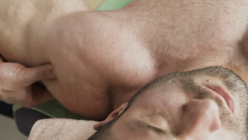 Close up view of massaging triceps of handsome athlete. 4K.   Shutterstock HD Video #1010630144