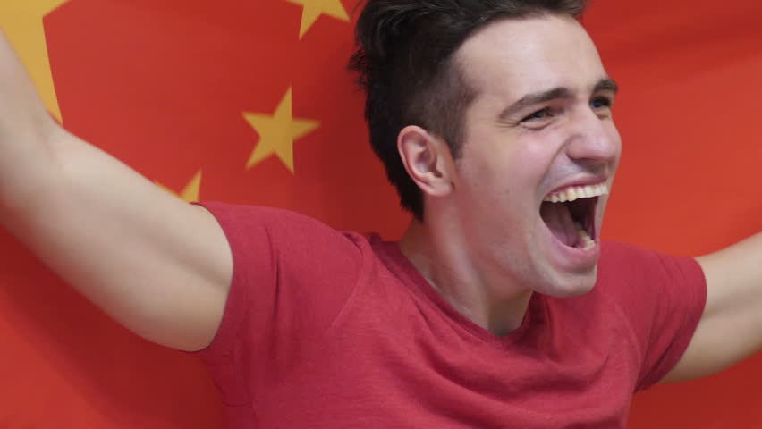 Chinese Young Man Celebrating while holding the Chinese Flag in Slow Motion