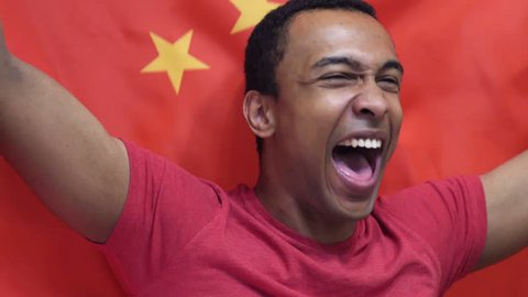 Chinese Fan Celebrating while holding the Chinese Flag in Slow Motion