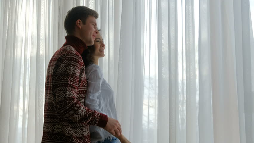 Couple home leisure. young man and woman standing near the window looking out pointing to something | Shutterstock HD Video #1010661194