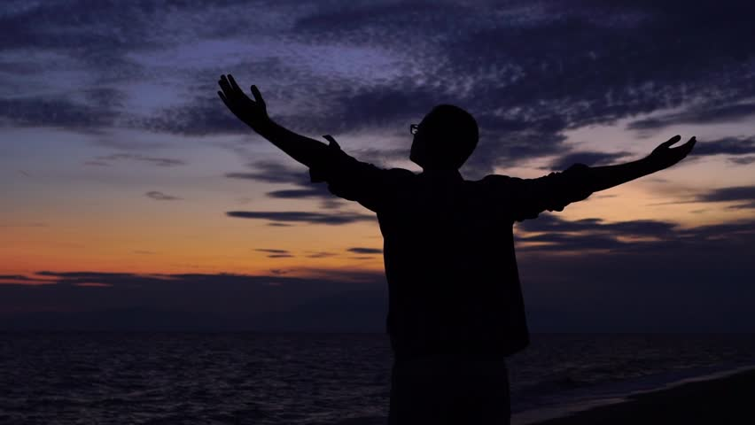 SLOW MOTION: Silhouette of a young man standing at the beach, looking at beautiful sunset, spreading hands and enjoying freedom | Shutterstock HD Video #1010699204