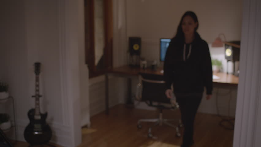 Female thinks of an idea and sits back down at desk to continue working HD stock video. Alexa camera