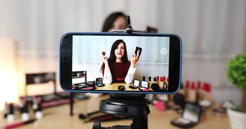 Makeup vlogger influencer creating cosmetic product explainer video. Young woman is filming a new episode for her personal make up vlog. Recording live tutorial video. Recording vlog on smart phone.