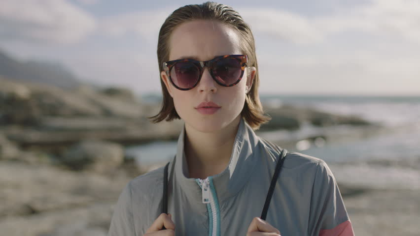 Portrait of attractive confident woman smiling wearing sunglasses at beach seaside | Shutterstock HD Video #1010716544