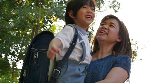Asian mother holding her son while walking in the park , back to school concept slow motion