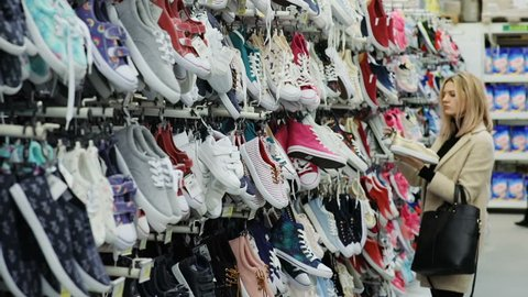 calm beautiful girl holding a pair of stylish sneakers while standing near a shelf of shoes in supermarket shopping mall warehouse blonde woman choosing new summer shoes in shoe store clothes business