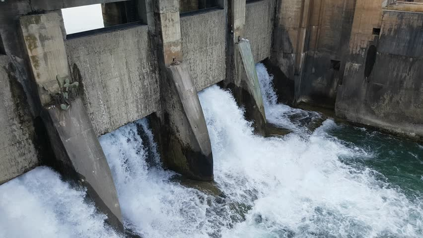 Spring flood water flowing on hydroelectric power station dam. | Shutterstock HD Video #1010763644