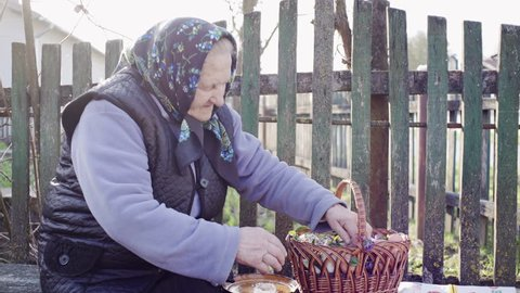Easter holiday in the Ukrainian village - the old authentic grandmother preparing the Easter basket on the bench in the courtyard.