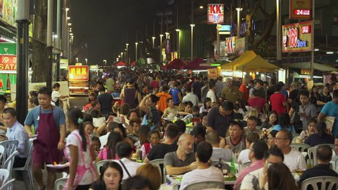 Crowd of people enjoy food on Jalan Alor food street at night - October 2017: Kuala Lumpur, Malaysia