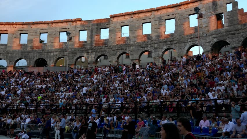 PULA, CROATIA, AUGUST 2017: Right to left pan over crowd of people sitting in the roman amphitheatre of Pula arena before the start of concert