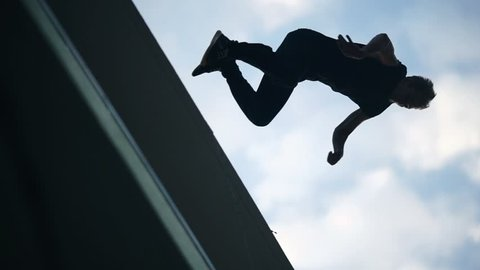 Acrobat man doing somersault and parkour jump on roofs buildings on city street bottom view. Street sport and extreme concept