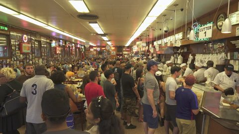 Busy restaurant. Men serving food in the counter. Katz's delicatessen - August 2017: Manhattan, New York City, NY, US