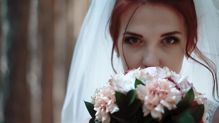 The bride stands near trees in the forest, brings a bouquet of flowers to face and looks at the camera, portrait, close-up #1010881214