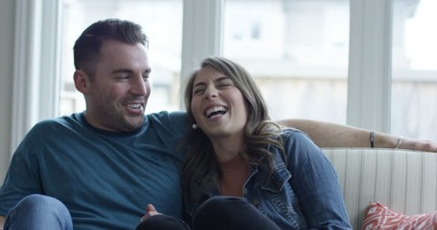 Happy young couple watching tv - impersonating characters and laughing