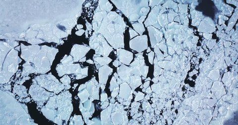 Flying above ice, top aerial view of arctic ice floes