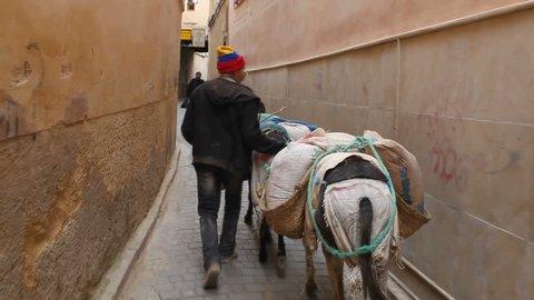 Fez - Circa February 2018: POV following donkey and man in Fez medina, Fez, Morocco