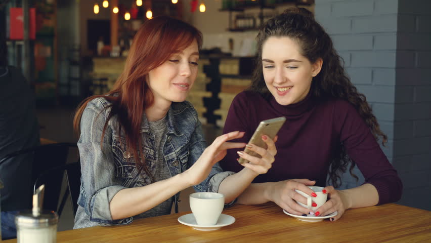 Pretty young girl is using smartphone and showing interesting photos to her female friend the discussing them while drinking coffee in nice modern cafe.