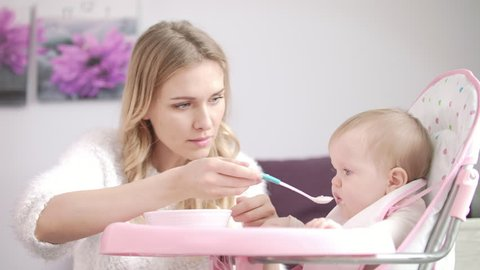 Mom feed child in baby chair. Woman feeding baby with porridge. Beautiful woman feeding little kid with baby food bowl. Mother with baby eating puree