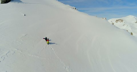 An aerial view of two mountaineers with skis and snowboards climbing on the top of a snowy mountain, Livigno, Italy, Europe