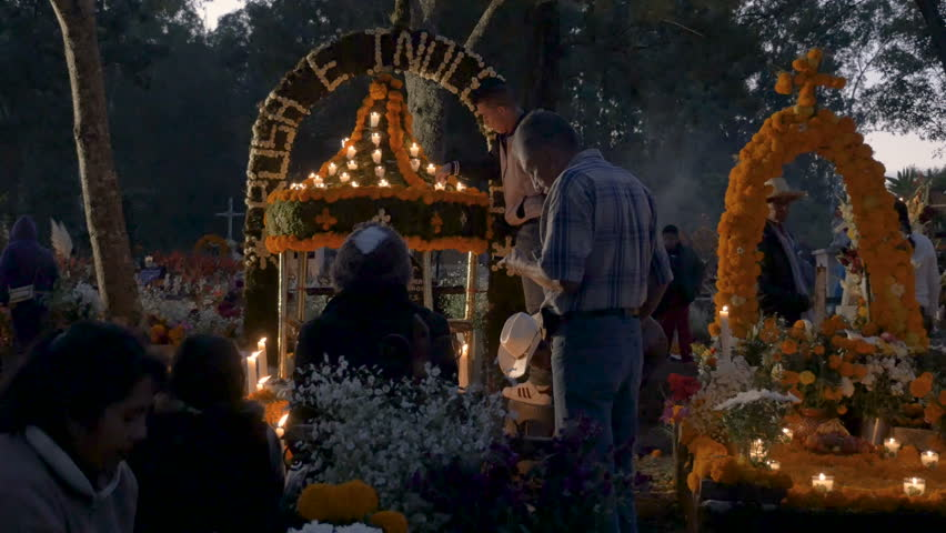 TZURUMUTARO, MEXICO - NOVEMBER 1, 2016 - Multi generational Mexican family standing in front of a day of the dead shrine in a busy graveyard