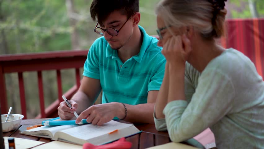 Teen boy works through problems on a marker board while his mother watches next to him. | Shutterstock HD Video #1010976134