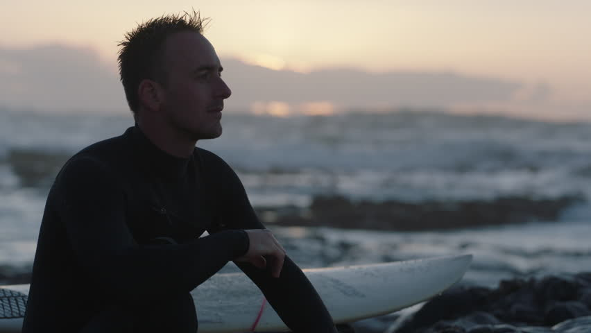 portrait of young surfer man sitting on beautiful seaside beach looking pensive, contemplative successful male thinking healthy lifestyle goals real people series #1010987174