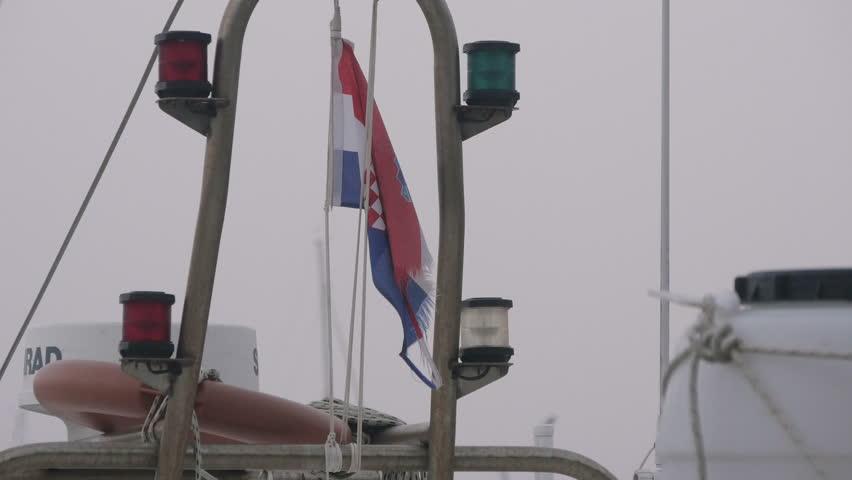 Novigrad, Croatia - April, 2016: Croatian flag hanging in the seaport of Novigrad on a foggy day   Shutterstock HD Video #1010987534