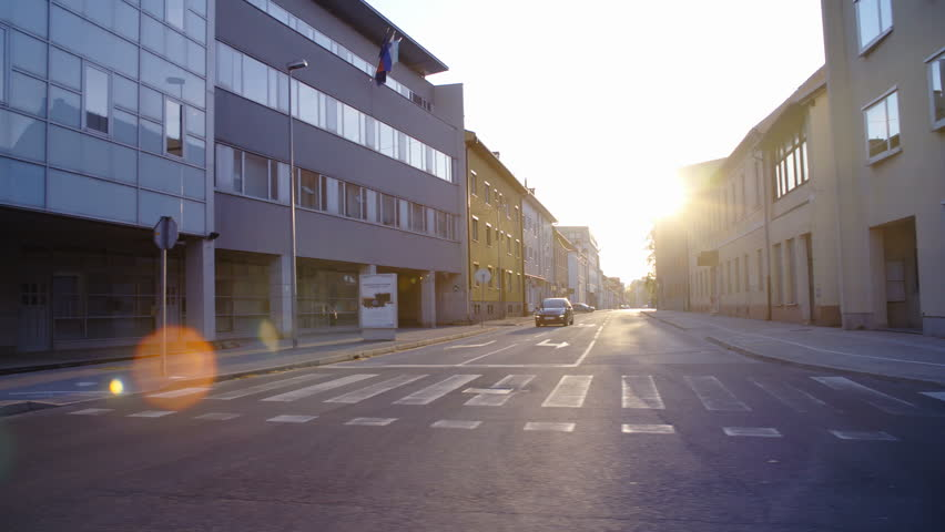 Car side window view of sunset shine on city street 4K. Wide shot of side street with sunset in background shining all over the surface. | Shutterstock HD Video #1010999804