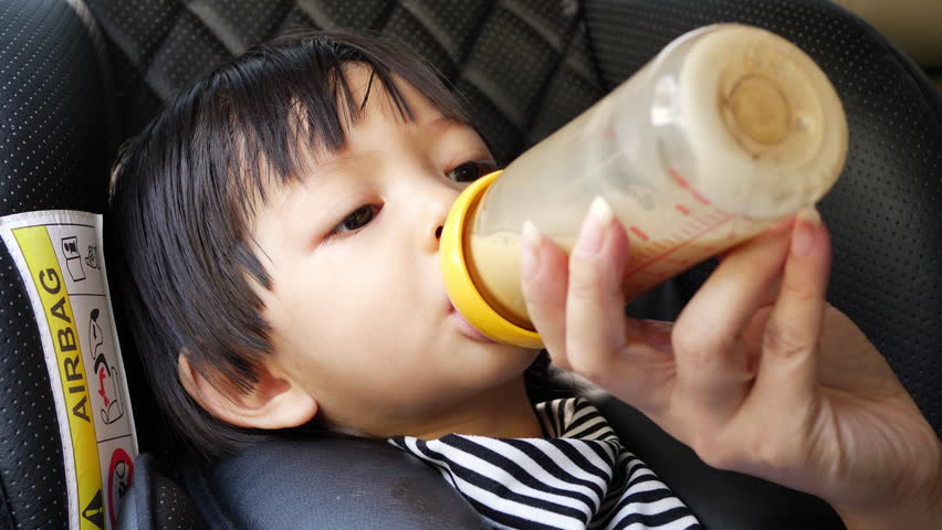 child sucking bottle milk in car seat with mom