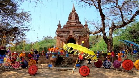 Colored handmade umbrella and beautiful string marionettes, fluttering on the wind next to the small Buddhist Shrine in archaeological site of old Bagan, Myanmar.