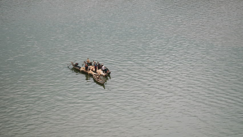 Upper view of small fishing boats on river lashed side by side to use a large fishing net