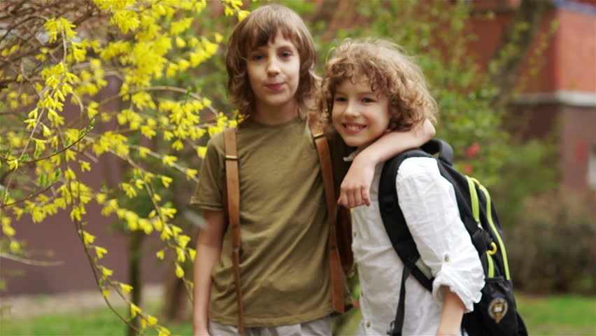 Two boys hug and look at the camera. School friends are laughing. Children have school bags behind them. Back to school. Children Day | Shutterstock HD Video #1011036584