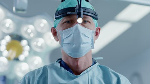 In the Hospital Operating Room Professional Surgeon Puts on Surgical Flashlight, Turns it on and Looks into Camera. Shot on RED EPIC-W 8K Helium Cinema Camera.