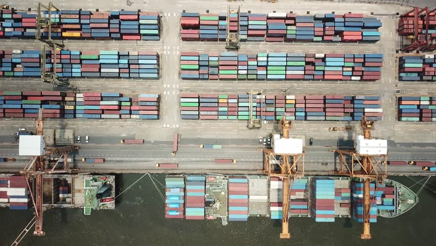 Container ship in export and import business and logistics in Thailand. Shipping cargo to harbor by crane. Water transport International. Aerial view  | Shutterstock HD Video #1011057824