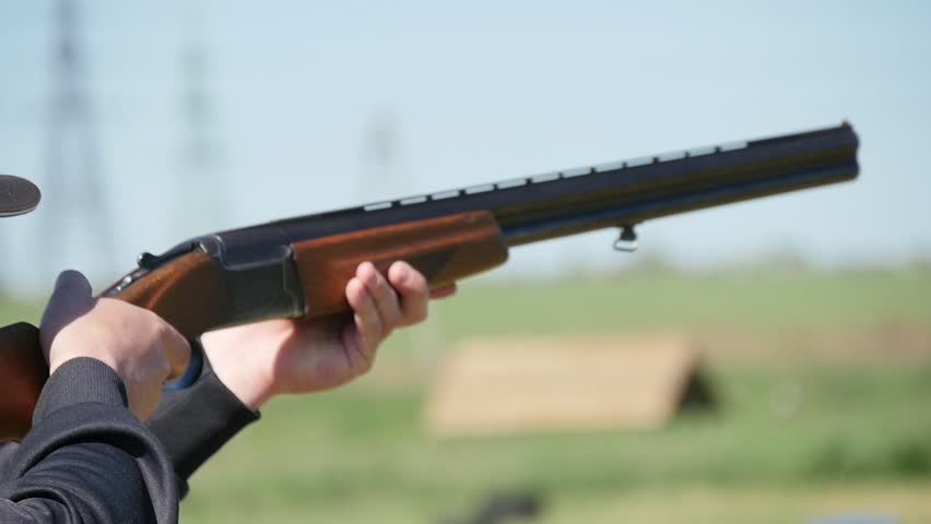 Closeup of a hunter keeping his modern double barrel gun, targeting and shooting at clay plates. The recoil rocks the rifle on a range in slo-mo #1011069014