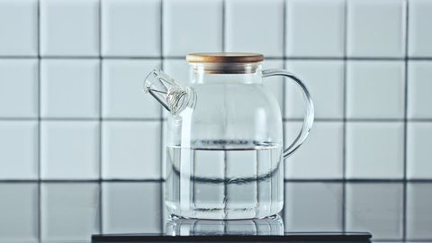 Water boiling in a transparent modern glass teapot (kettle)