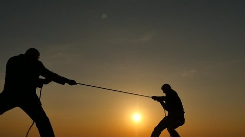 competition concept - tug of war - 2 persons pulls rope silhouettes