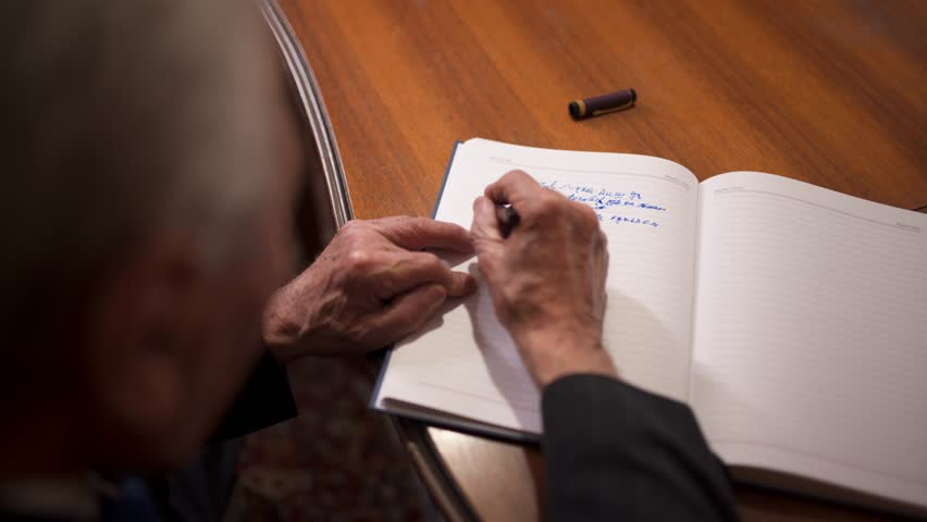 Old man writing with pen. Elderly gentleman uses pen with ink to write on paper, at his home.
